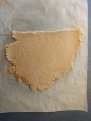 Étaler la pâte à sablé de Noël entre deux feuilles de papier cuisson