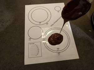 Verser 1 cuillère de chocolat sur le papier guitare posé sur le guide