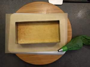 Puncher un second biscuit des deux cotés et le poser sur la crème. Pocher la ganache et y cacher les écorces d'orange confites