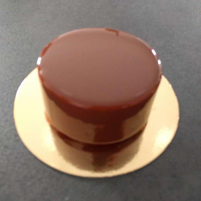 Glaçage miroir au chocolat au lait appliqué sur un entremets