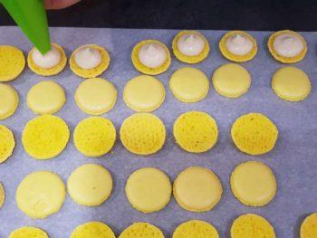 Pocher la préparation sur les macarons, d'une taille de noix