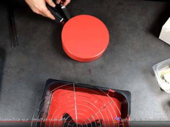 Soulever l'entremet et le déplacer en forme de cercle au dessus de la grille pour couper les coulures, puis, le déposer sur un carton doré