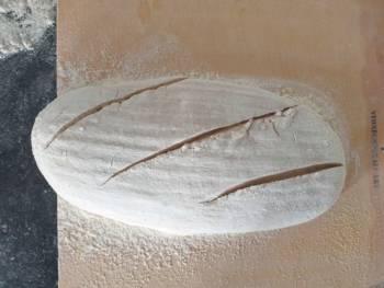 Retirer l'excédent de farine, scarifier à l'aide d'une lame de rasoir